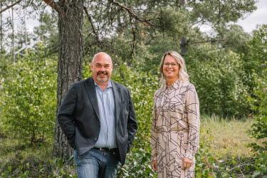 En man och en kvinna tittar in i kameran, bakom dem är en skog.