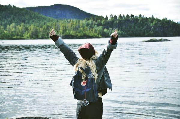 En flicka blickar ut mot vattnet md armarna upp i skyn