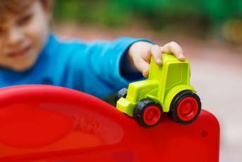 Bilden visar ett barn med en leksakstraktor