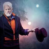 Bilden föreställer Ronny Eriksson som står ute i naturen och håller i en rutig hatt