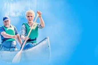 Bilden föreställer en blå bakgrund med en tjej o en kille som paddlar kanot