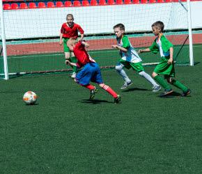 Fyra pojkar spelar fotboll på en fotbollsplan.