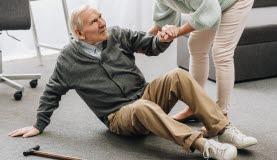Bilden föreställer en äldre man som ligger på golvet och får hjälp upp av en annan person.