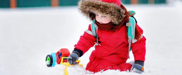 Bild på ett barn som leker med en traktor i snön.
