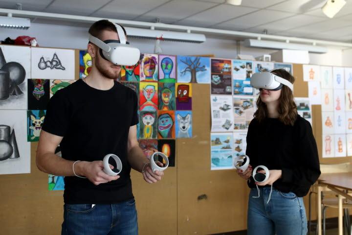 Två elever står i ett klassrum med VR-glasögon på sig.