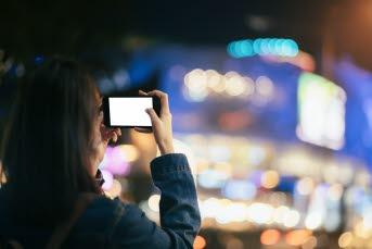 Bilden föreställer en tjej som håller en telefon