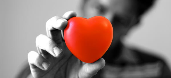 Bilden visar en hand som håller ett rött hjärta