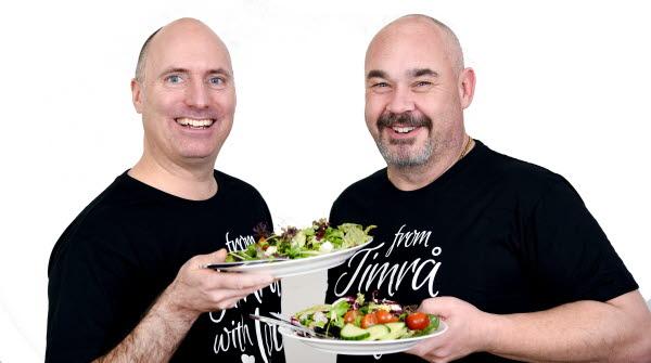 Bilden föreställer kommunchefen och näringslivschefen som håller i en tallrik med mat.