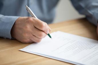 En hand håller i en penna och skriver under ett dokument.