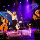 Bilden föreställer artisten Fröken Elvis som står på scenen och sjunger med sitt band
