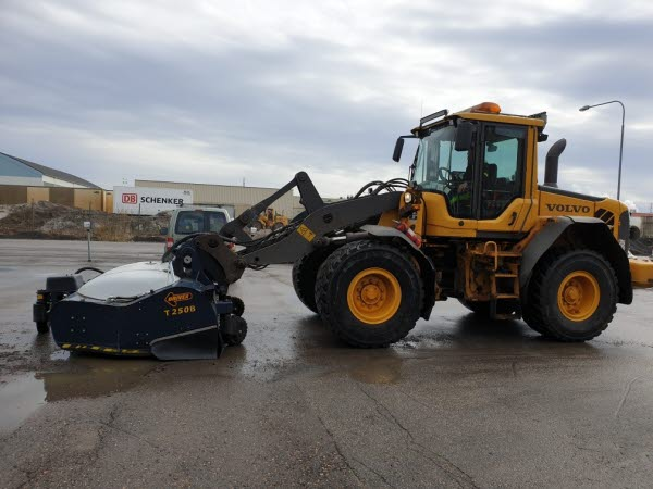 Bilden föreställer en traktor som sopar upp sand