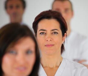 Vårdpersonal med vita arbetsskjortor. Två kvinnor i förgrund och två män i bakgrund.