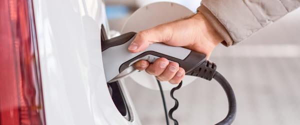 En person håller en elbilsladdare i handen mot uttaget på en vit elbil. Personen har en beige dunjacka.
