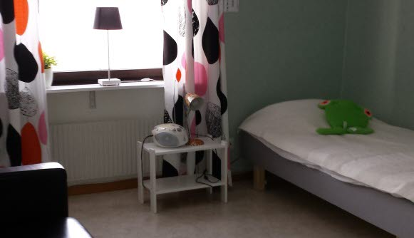 Bilden visar ett enkelt möblerat sovrum