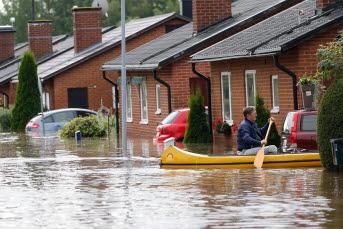 Bilden föreställer en person som paddlar kanot vid ett bostadsområde.