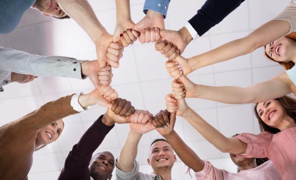 Bilden visar människor som håller händerna tillsammans i en cirkel