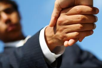 Bilden föreställer två människor som tar i hand
