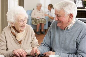 Bilden visar två äldre personer som skrattar tillsammans