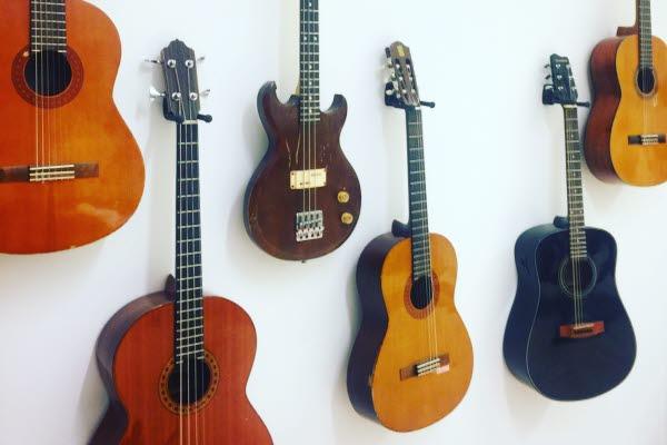 Bild på flera gitarrer som hänger på en vägg.