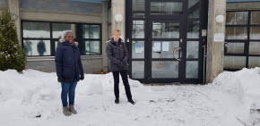 Två kvinnor står framför en byggnad med fönster och en stor port med glas i bakgrunden. Kvinnorna har mörka vinterjackor på sig och marken är täckt av snö.