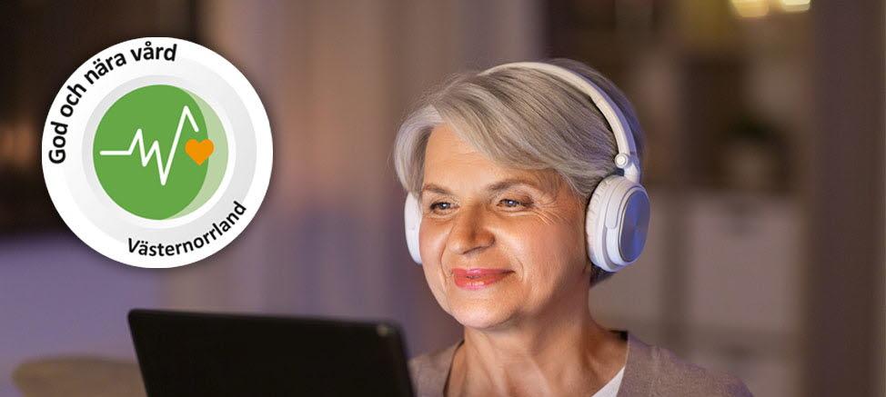 Kvinna läser på en ipad och lyssnar i hörlurar