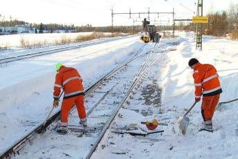 Bilden föreställer två personer som snöröjer på järnvägsrälsen.