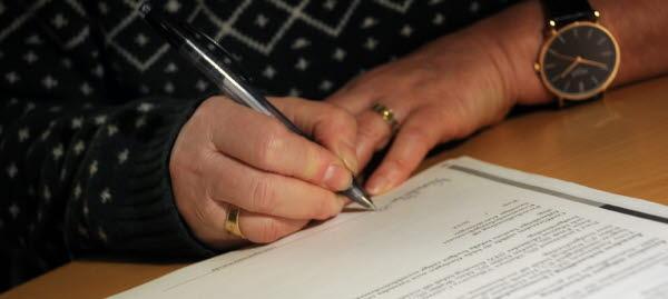 Bilden visar händer på en person som skriver under ett papper