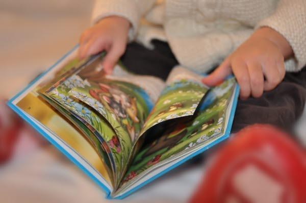 Ett barn som läser en barnbok.