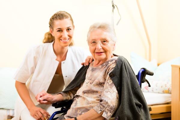 Bilden föreställer en äldre rullstolsburen kvinna med ett vårdbiträde vid hennes sida.