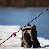 Bilden föreställer en ryggsäck och ett fiskespö som står på snön vid ett vattendrag
