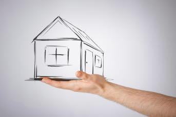 Bilden föreställer en hand som håller i ett skissat hus.