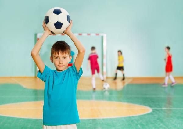 Pojke i blå tröja håller i fotboll med armarna ovanför huvudet. Barn i bakgrunden spelar fotboll.