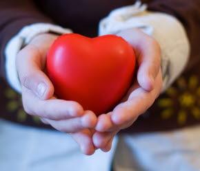 Bilden föreställer två händer som håller i ett hjärta.