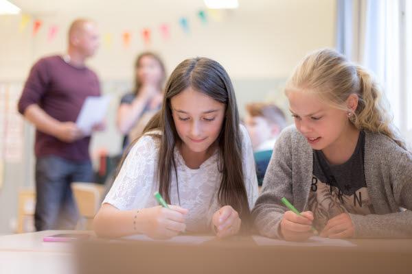 Två elever sitter vid ett bord i ett klassrum.