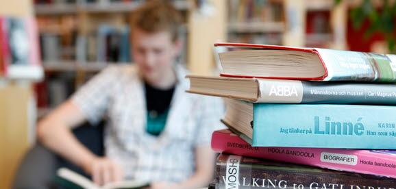 Bilden visar en hög biblioteksböcker i förgrunden med en suddig läsande person i bakgrunden