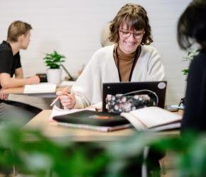 Tre elever sitter runt bord. På bordet ligger block och en uppfälld Chromebook. I förgrunden syns gröna växter.