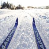 Bilden föreställer ett par skidor som åker i ett skidspår en solig vinterdag