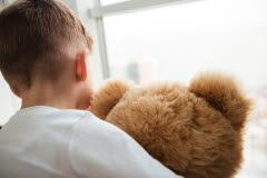 En liten pojke sitter med ryggen emot och håller i en brun nallebjörn. Pojken har en vit långärmad tröja och tittar ut genom ett fönster.