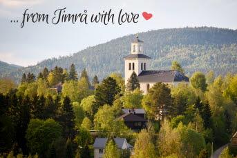 """Vy över en kyrka framför ett berg, kyrkan är omgiven av träd. Mot en blå himmel står """"...from Timrå with love"""" i svart med ett rött hjärta till höger om texten."""