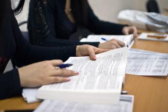 Bilden föreställer en kvinnnas hand som håller i en bok.