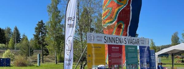 """Framför konstverket Y:et står fyra skyltar i gult, rött, grönt och blått med rubriken """"Sinnenas vägar"""""""