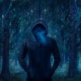 Bilden föreställer en mörkklädd man i en skog