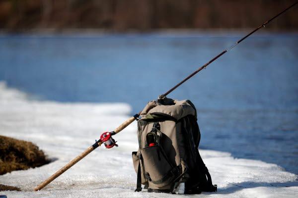 Bilden föreställer en ryggsäck och ett fiskespö som står på snön vid ett vattadrag