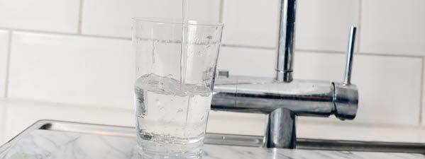 Bilden föreställer en kökskran som häller vatten i ett glas