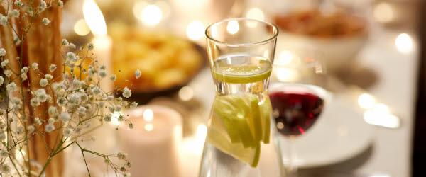 Dukat bord med vattenkaraff, rostad kyckling och en vas med stjärngräs.