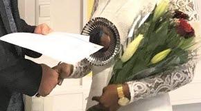 Bilden visar stipendieöverlämning med blombukett