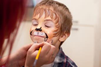 Bild på ett barn som får ansiktet målat med ansiktsfärg.