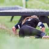 Bilden föreställer en kvinna som kryper under ett hinder vid Obstacle Race