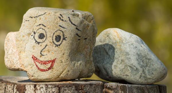 Bilden visar en sten med ett leende ansikte