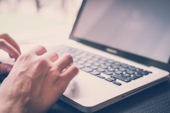 Bilden föreställer en hand som skriver på en dator.